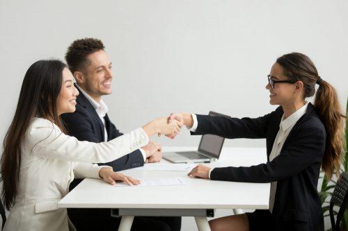 Smiling Diverse Businesswomen Shake Hands Group Meeting Deal Concept